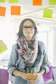 Portrait of smiling businesswoman standing by glass wall with sticky notes in office