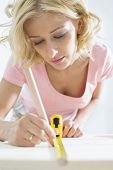 Beautiful woman marking table with measure tape
