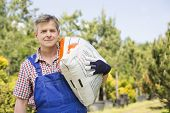 Portrait of gardener carrying sack in plant nursery