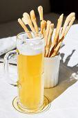 Mug Of Beer And Bread Sticks On Table