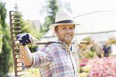 Portrait of smiling gardener carrying rake on shoulders at plant nursery