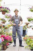 Full-length portrait of happy gardener standing at greenhouse