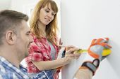 Couple using tape measure on wall