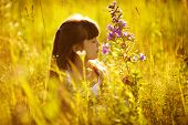 Happy Little Girl Smelling A Flower