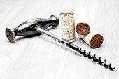 Corks and corkscrew on a wooden background
