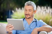 Male doctor looking at tablet PC at nursing home porch