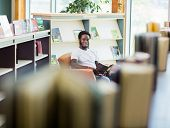 Portrait of smiling male student reading book in library
