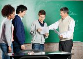 Happy male professor giving exam result to student with classmates standing in a row at classroom
