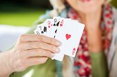 Midsection of senior woman showing playing cards at nursing home