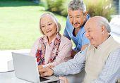 Male caretaker watching senior couple using laptop at nursing home porch