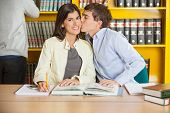 Portrait of young woman smiling while man kissing her at table in university library