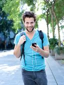Young Man Walking Outdoors With Mobile Phone
