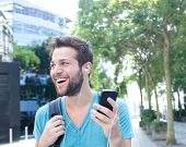 Young Man Smiling With Mobile Phone And Earphones