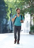 Cheerful Young Man Walking With Mobile Phone And Bag