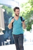 Student Walking On Campus With Mobile Phone