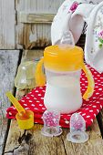 stock photo of teats  - baby feeding bottle with milk on old wooden table - JPG