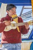 PUNO, PERU, MAY 5, 2014: Local man plays music on traditional instruments during boat trip to Uros Islands
