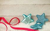 Blue stars and a red ribbon on wooden background