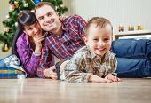 Beautiful Young Family Under The Christmas Tree At Home