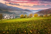 Village On Hillside Meadow With Forest In Mountain At Sunrise