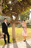 Young bride and groom couple posing in the park