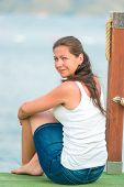 Charming Brunette Resting Sitting On A Pier Near The Sea