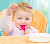 cute one year old girl in a highchair  with a spoon and a plate in the kitchen at home