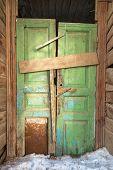 Crooked Green Door In Old Wooden House.