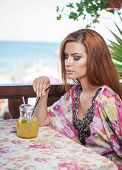 pic of woman red blouse  - Attractive red hair young woman with bright colored blouse drinking lemonade on a terrace - JPG