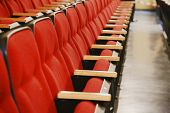 picture of stage decoration  - Oblique view over a row of red theatre seats at a movie theatre - JPG