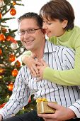 Portrait of a smiling couple holding gifts at Christmas tree