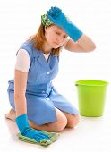 tired woman cleaning the floor with a rag