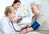 Female doctor measuring blood pressure of senior woman