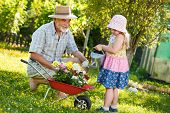 Happy grandfather with his granddaughter pouring flowers in the garden
