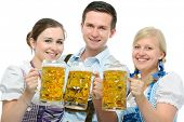 group of young people in traditional bavarian tracht holding Oktoberfest beer steins