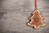 Gingerbread christmas tree hanging over wooden background