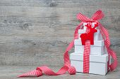 Stack of Christmas gifts with ribbon and bow  on old wooden background