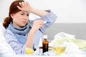 image of high fever  - Sick woman  lying in bed with high fever - JPG