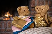 Couple vintage teddy bears with christmas gifts in front of fireplace