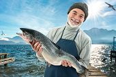 stock photo of atlantic ocean  - Fisher holding a big atlantic salmon fish in the fishing harbor - JPG