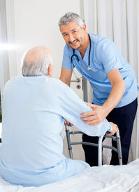 picture of zimmer frame  - Portrait of smiling male caretaker helping senior man with walking frame in bedroom at nursing home - JPG