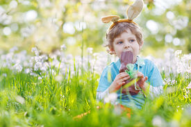 image of eat grass  - Cute happy little child wearing Easter bunny ears at spring green grass and blooming apple garden eating chocolate bunny and having fun outdoors - JPG