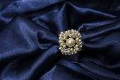 stock photo of brooch  - brooch for scarf with pearl on a blue background - JPG