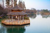 pic of gazebo  - Round traditional Chinese wooden gazebo on the coast of West Lake park in Hangzhou city China - JPG