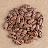 stock photo of pinto bean  - Top view of circle of pinto beans against brown vinyl background - JPG