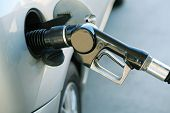 image of fuel pump  - A fuel pump in the filling up the gas tank of a silver car - JPG