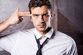 stock photo of handgun  - Tired young man in shirt and tie gesturing handgun near his head and looking at camera - JPG