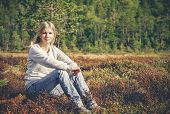 stock photo of scandinavian  - Young Woman sitting alone walking outdoor Travel Lifestyle scandinavian forest nature on background - JPG