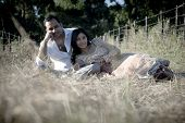 picture of indian beautiful people  - Beautiful young Indian couple relaxing outdoors in long grass - JPG