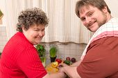 image of disability  - a mentally disabled woman and a young man cooking together - JPG